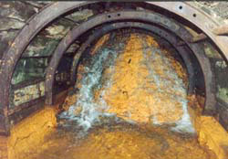 Acidic water pours over roof-high shale dam in No 9 adit, Cwmrheidol mine, 1992